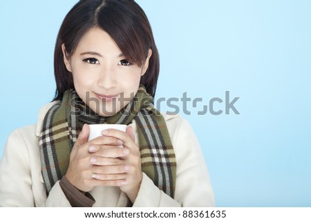 beautiful woman wearing winter clothing and holding coffee cup