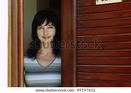 Beautiful woman welcomes at the wooden door - stock photo