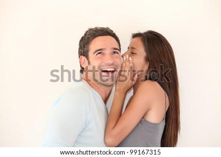 Beautiful woman whispering to boyfriend's ear - stock photo