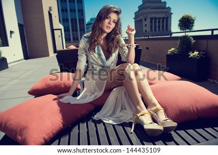 Beautiful woman white skirt, high heels, and jeans jacket sitting the bed on the rooftop - stock photo
