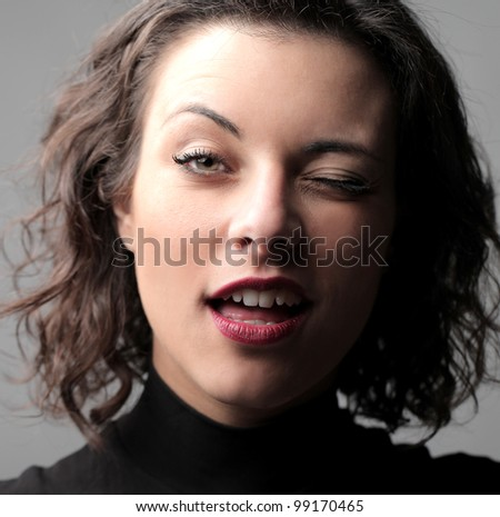 Beautiful woman winking with her eye - stock photo
