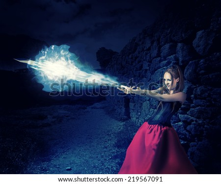 beautiful woman witch trains in medieval castle cast magic - blue cold ball of ice from hands - stock photo