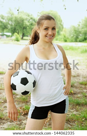 Beautiful woman with a ball in his hands at the beach - stock photo