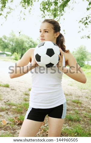 Beautiful woman with a ball in his hands at the beach