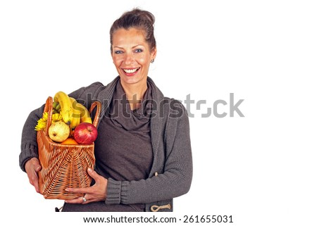 Beautiful woman with a basket full of fruits and flowers - stock photo