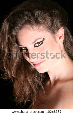 Beautiful woman with a bewitching smile looking evil - stock photo