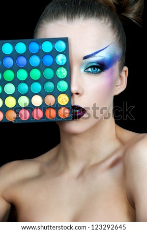 Beautiful woman with a bright makeup holding the box with the shadows to his eyes. Make-up artist - stock photo