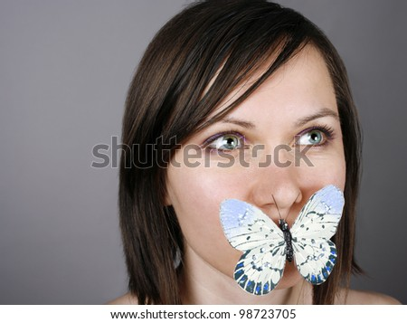 Beautiful woman with a butterfly on lips - stock photo