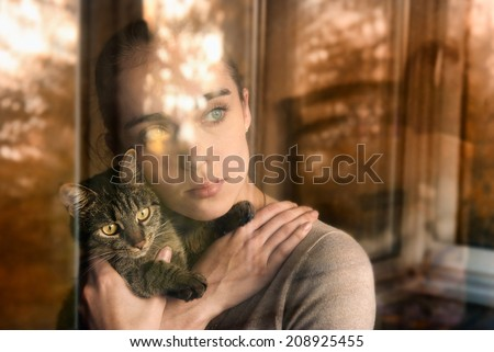 Beautiful woman with a cat and sits by the window - stock photo