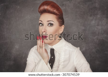 Beautiful woman with a confused expression on the blackboard background - stock photo
