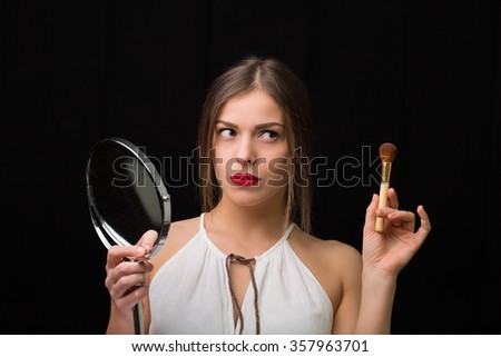 Beautiful woman with a cosmetic mirror and makeup brush - stock photo