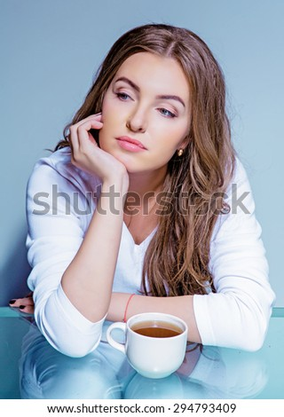 beautiful woman with a cup of coffee against blue background - stock photo