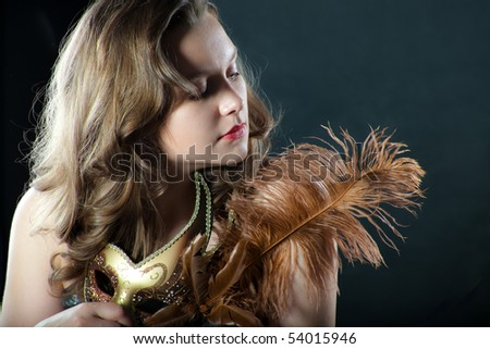 Beautiful woman with a feather and mask on black background - stock photo