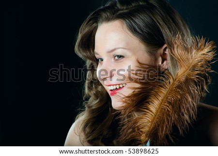 Beautiful woman with a feather on black background - stock photo