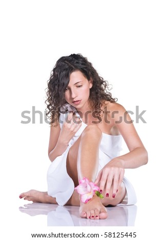 Beautiful woman with a flower during body care procedure isolated on white - stock photo