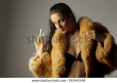 beautiful woman with a fur drinking wine - stock photo