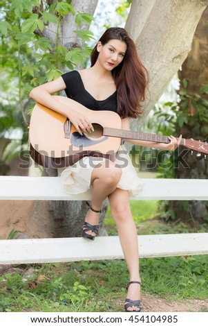 Beautiful woman with a guitar against a background of natural li