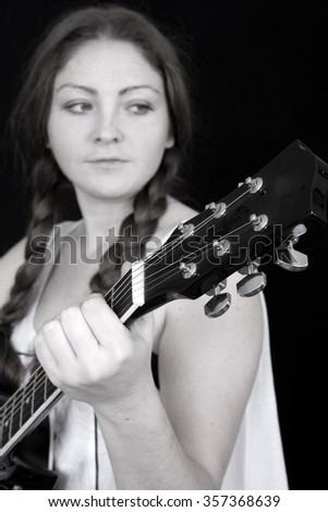 Beautiful woman with a guitar on a black background - stock photo