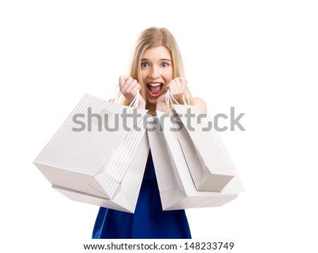 Beautiful woman with a happy face holding shopping bags, isolated on a white background - stock photo