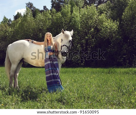 beautiful woman with a horse in the forest - stock photo