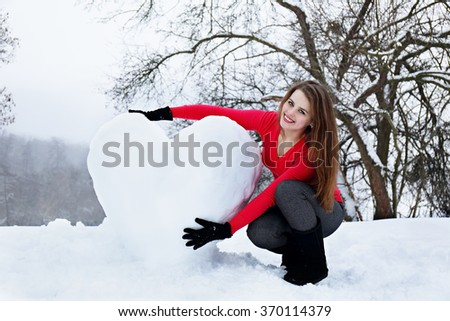 Beautiful woman with a huge heart made of snow - stock photo