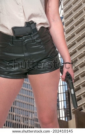 Beautiful woman with a loaded handgun pistol - stock photo