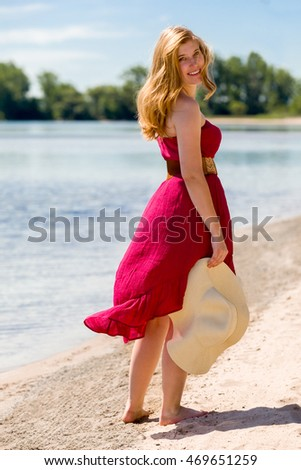 Beautiful woman with a red sun-dress walking along the beach