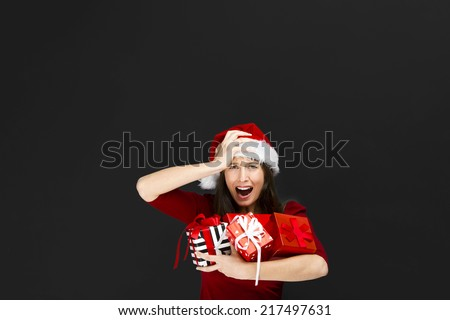 Beautiful woman with a santa hat over a black background and holding christmas gifts - stock photo