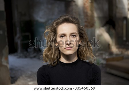 Beautiful woman with a serious expression on her face looking straight ahead with a view of abandoned building in the background