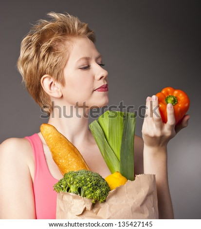 Beautiful woman with a shopping bag full of fruits and vegetables