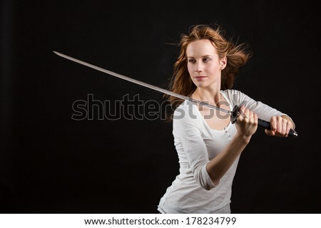Beautiful woman with a sword, blade is slightly blurred - stock photo