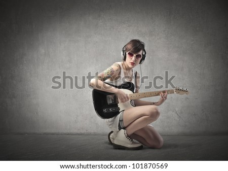 Beautiful woman with a tattoo on her arm playing the guitar - stock photo