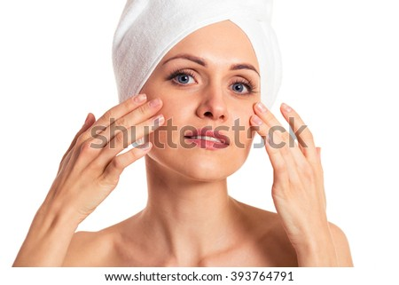 Beautiful woman with a towel on her head is looking at camera and touching her face, isolated on a white background