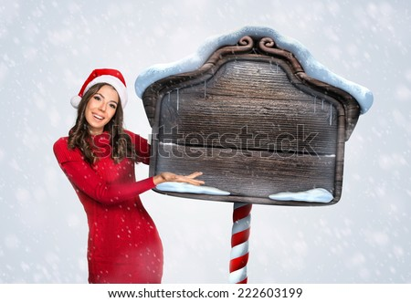 Beautiful woman with a wooden Christmas sign  - stock photo