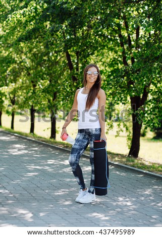 Beautiful woman with a yoga mat and a shaker with water in hand. Attractive girl goes to the gym with yoga mat and a backpack in hand - stock photo