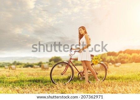Beautiful woman with an old red bike in a wheat field - stock photo