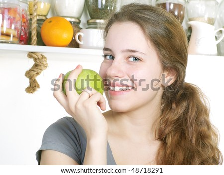 Beautiful woman with apple in her kitchen