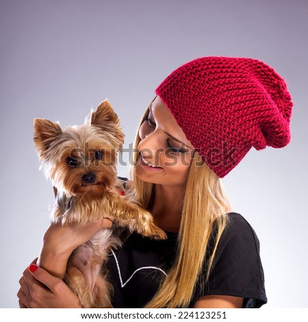 Beautiful woman with autumn fashion - Embracing yorkshire terrier dog - stock photo