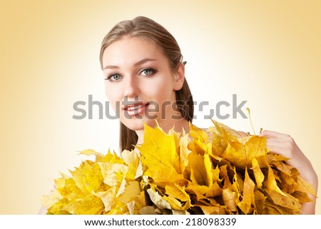 Beautiful woman with autumn leaves on yellow background. Lady with a wreath of autumn leaves.  - stock photo