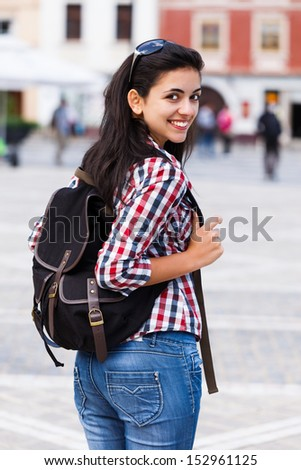 Beautiful woman with backpack looking at the camera, smiling. - stock photo