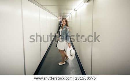 Beautiful woman with bags walking at boarding gate at airport - stock photo