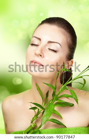 Beautiful woman with bamboo plant on a green background. SPA - stock photo