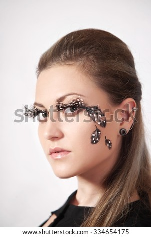 Beautiful woman with big eyelashes and face-art, studio shooting