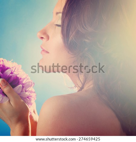 beautiful woman with big flower on blue background