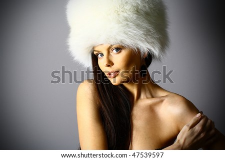 Beautiful woman with big white fur hat over gray background. - stock photo