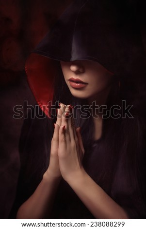 Beautiful woman with black cloak over black background - stock photo