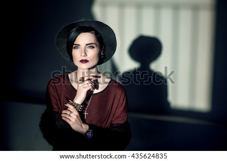 Beautiful woman with black hair, dark lipstick and a hat standing in a dark room lit by a single source, and casts a shadow on the wall
