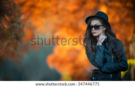 Beautiful woman with black hat and sunglasses posing in autumnal park. Young brunette spending time during autumn in forest. Portrait of attractive girl with creative makeup, outdoors shot during fall - stock photo