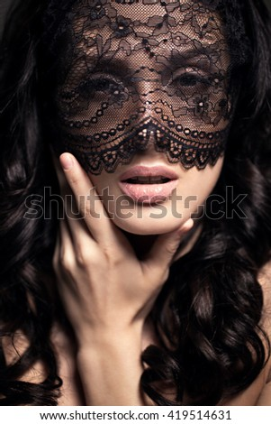 Beautiful Woman with Black Lace mask over her Eyes.  Sexy Lips and Nails closeup. Sensual Mouth. Manicure and Makeup. Makeup concept. Passion. Closeup portrait. - stock photo