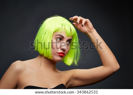 beautiful woman with black nails wearing colorful short hair wig on black background  - stock photo